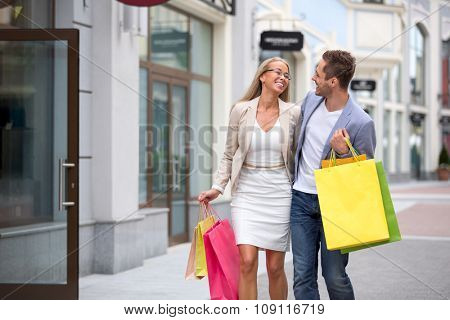 Young couple with bags in outlet