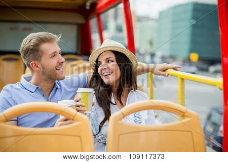 Young couple with a cup in the tour bus