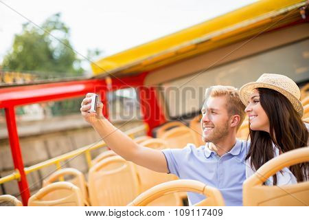 Young couple making self at the tour bus