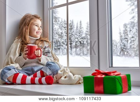 little girl sitting by the window and looking at the winter forest