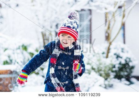 Happy child having fun with snow in winter