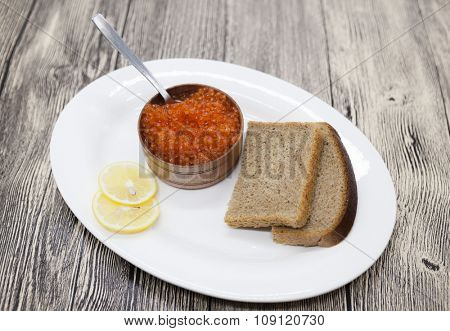 Fresh appetizing red salmon caviar in a wooden jar with pieces of bread on a porcelain platter