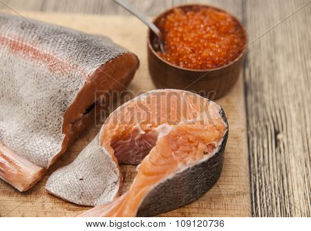 Fresh Norwegian rainbow trout with red caviar on a wooden background.