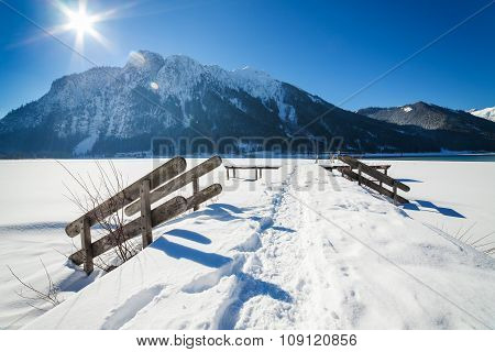 Mountain winter landscape with wooden stairs covered with snow