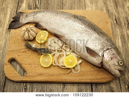 Fresh Norwegian rainbow trout with lemon and onions on a wooden background.