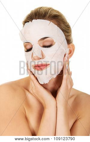 Young woman with facial mask, isolated on white