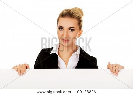Smiling businesswoman holding empty banner.