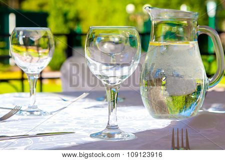 Glasses and white tablecloth on table in summer
