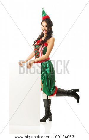 Full length woman wearing elf clothes holding white banner on the floor.