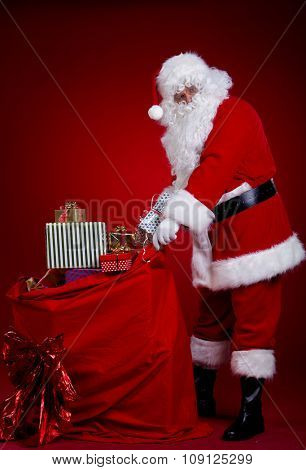 Santa Claus carrying big bag ,on red background