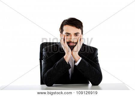 Smiling businessman sitting at the desk.