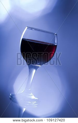 Glass of red wine in cold blue tone with flare.