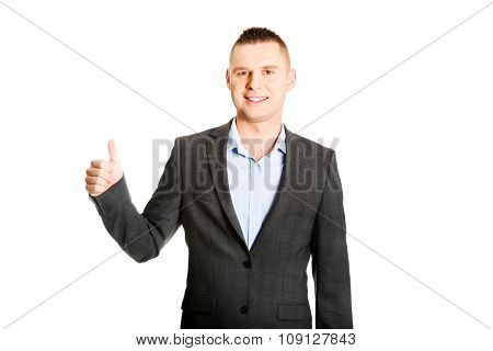 Young smiling businessman gesturing thumbs up.