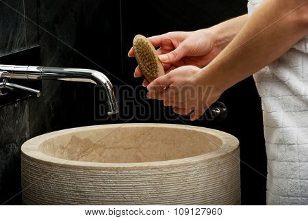 Woman cleaning nails with brush in bathroom.