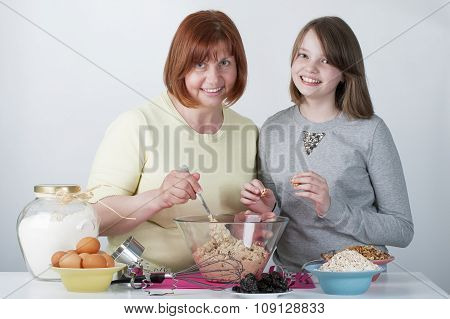 Mother And Daughter Knead The Dough For Cookies..