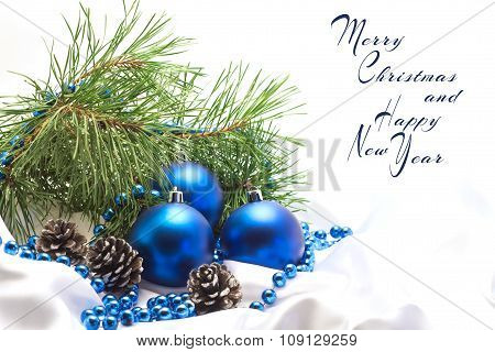 blue Christmas balls with pine branches and pine cones on a whit