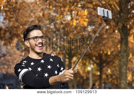 Young hipster taking a picture with a selfie stick