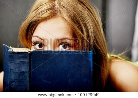 Teenage woman reading a book on the sofa.