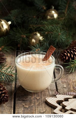 Traditional eggnog homemade christmas non alcohol winter drink in glass cup with cinnamon stick on v