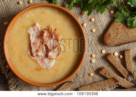Tasty pea soup yellow traditional homemade food with bacon and croutons on vintage wooden table back