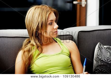 Young teenage woman with a pen on sofa.