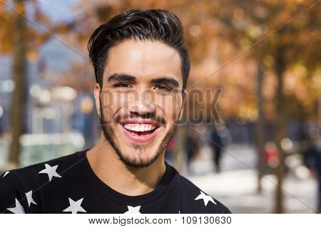 Headshot of a young latin man in an autumn day at a park