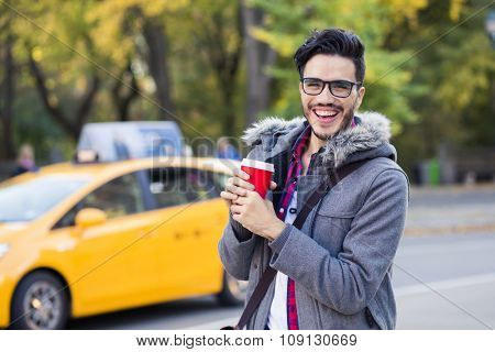 Young man with a cup of coffee in New York city, taxi passing by.