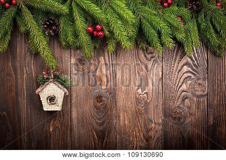 Fir Tree And Birdhouse On Dark Wooden Background