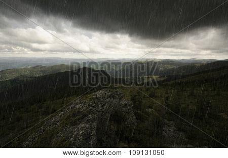 Rain falling over mountain landscape
