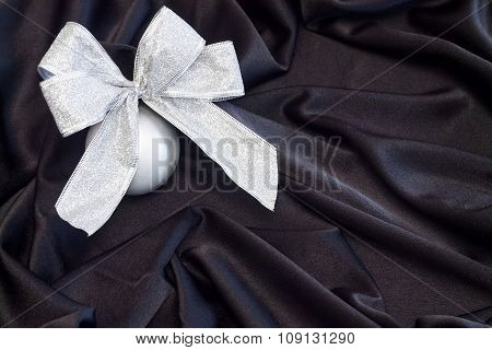 Grey Christmas ball with silver bow on black flowing fabric