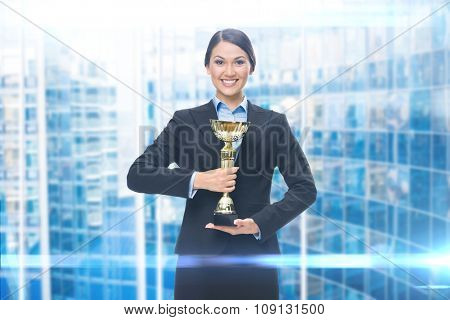 Portrait of businesswoman with golden cup, blue background. Concept of win and success