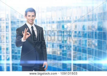 Portrait of ok gesturing businessman, blue background. Concept of leadership and success