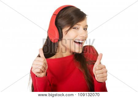 Young woman with thumbs up listening to music.