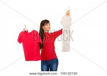 Confident young woman choosing shirt.