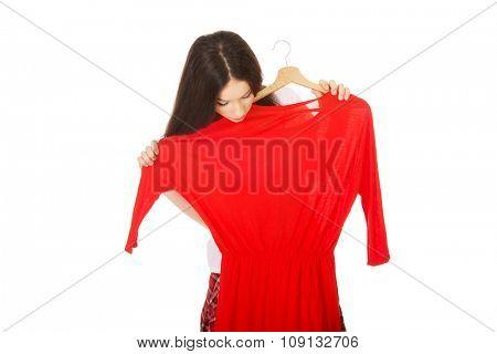 Beautiful teen woman buying red dress.