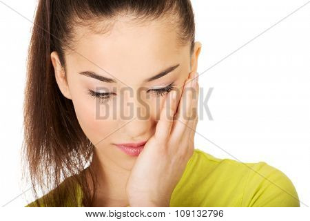 Teen woman with a toothache touching face.