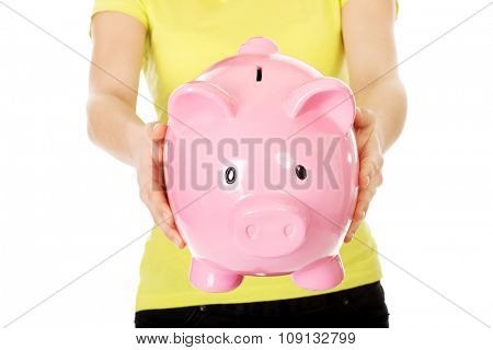 Woman's hands holding big piggybank.