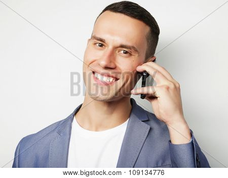 Young trendy man talking on cellphone, over white background