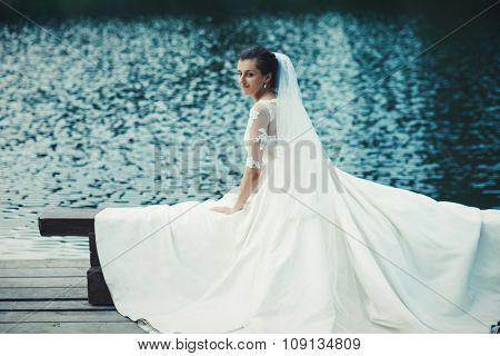 Young beautiful bride outdoors near lake.
