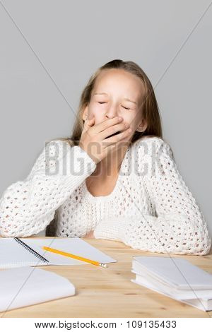 Schoolgirl Yawning Beside Textbooks