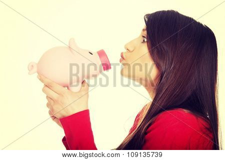Happy student woman  kissing a piggybank.