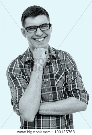 Blue toned black and white portrait of young man wearing glasses and checkered shirt standing with fist under his chin and laughing - laughter concept