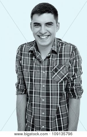 Blue toned black and white portrait of young smiling man wearing checkered shirt