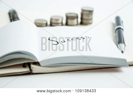 Put a pen on notebook,  beside success.. coins set up in  graph, line chart. business concept for