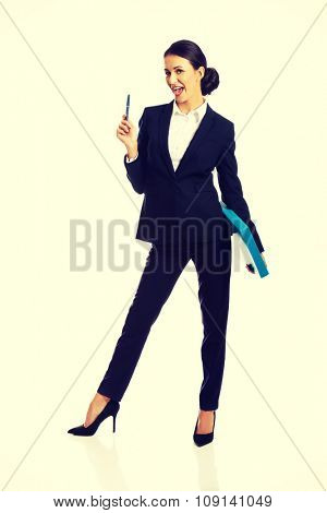 Happy businesswoman holding a pen and binder.