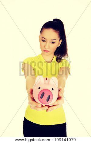 Sad teenage woman holding piggybank.