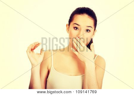 Young shocked woman with pregnancy test.