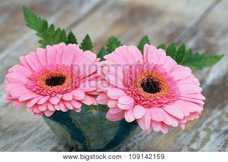 Pink gerbera daisies in flower vase on rustic wooden surface with copy space