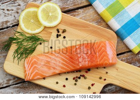 Raw salmon steak, lemon, fresh dill and black pepper on wooden board