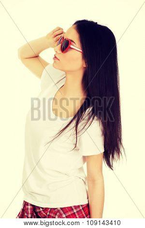 Teenage woman wearing heart sunglasses.